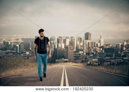 Man walking on road with city in the background. Direction concept