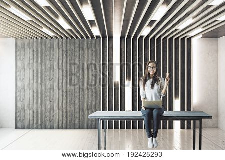 Girl with laptop sitting on table and showing peace sign in modern interior with empty wall. Mock up 3D Rendering