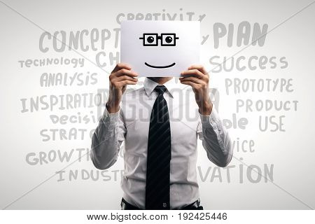 Businessman covering head with smiley drawn on poster. Light background with motivational words. Success concept