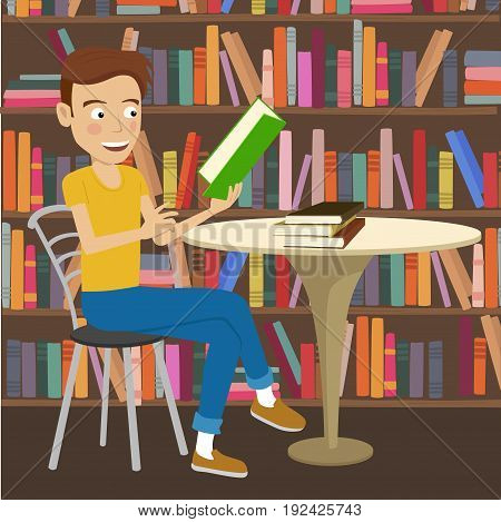 Male student reads a textbook sitting at the table in college library