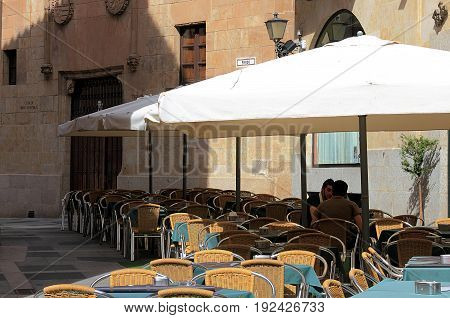 Salamanca, Spain - May 7, 2014: Two men talking on sunny afternoon on a restaurant patio in Salamanca, Spain.