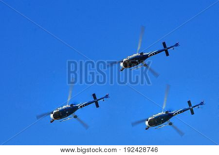three civilian helicopter in the blue sky.