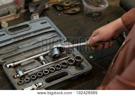 Mechanic take tool from the set tools wich lying on the desktop in garage