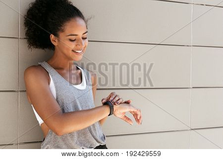 Fitness woman taking a break, checking activity tracker poster