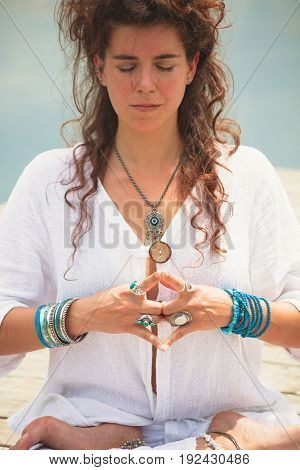 woman hands in yoga symbolic gesture mudra wearing lot of bracelets and rings outdoor closeup by the lake summer day