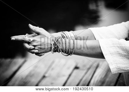woman hands in yoga symbolic gesture mudra wearing lot of bracelets and rings outdoor closeup by the lake summer day bw