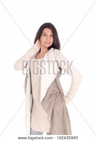 A young Hispanic woman standing the front in a deerskin coat with one hand on her head isolated for white background.