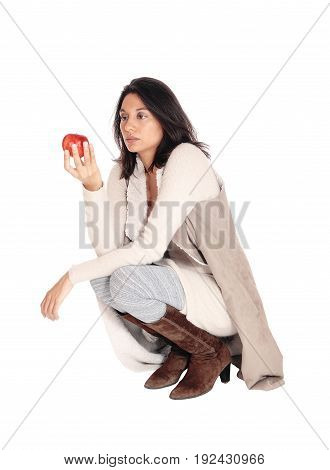 A beautiful Hispanic woman crouching on the floor holding a red apple isolated for white background.