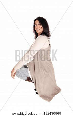 A young Hispanic woman crouching on the floor in a deerskin coat looking into the camera isolated for white background.