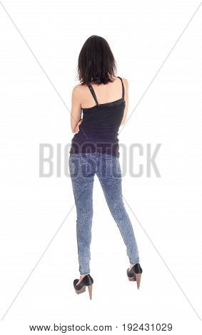 A beautiful young Hispanic woman in a black t-shirt and blue tights standing from the back isolated for white background.