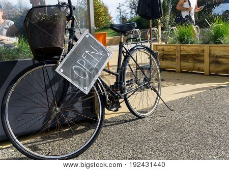Old bicycle with blackboard open sign hanging on it.