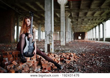 Red Haired Punk Girl Wear On Black And Red Skirt, With Bass Guitar At Abadoned Place. Portrait Of Go