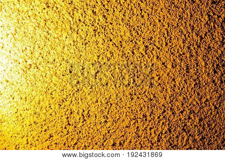 Plaster on a wall in gold lighting as a background .