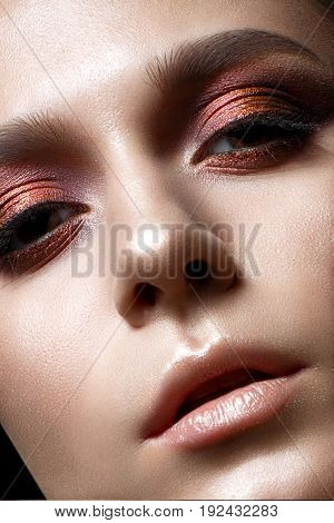 Young girl with bright evening makeup. Beautiful model with creative makeup and perfect shining skin. Beauty of the face. Photo taken in the studio. Close-up portrait.