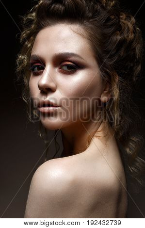 Young girl with bright evening makeup and hairdo with curls. Beautiful model with creative makeup and perfect shining skin. Beauty of the face. Photo taken in the studio.