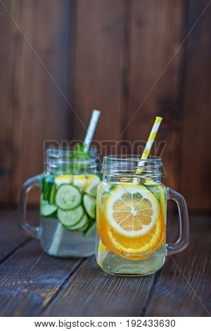 Detox water with cucumber lemon and mint. Lemonade with orange. Wooden background. The concept of a diet a vegetarian healthy food and a lifestyle.