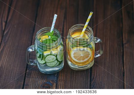 Detox water with cucumber lemon and mint. Lemonade with orange. Top view. The concept of a diet a vegetarian healthy food and a lifestyle.