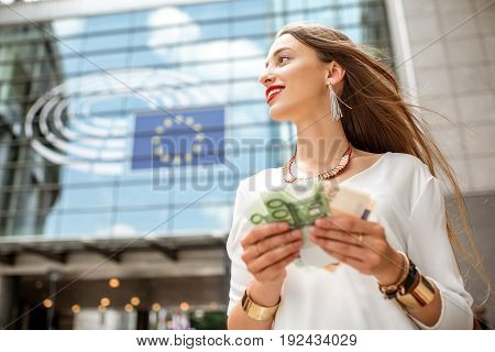 Woman holding euro banknotes in front of the Parliament building of European Union in Brussel city