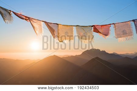 sunrise in the mountains fluttering colorful prayer flags. meditation design
