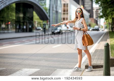 Young businesswoman trying to catch a taxi in the modern district of Brussel city