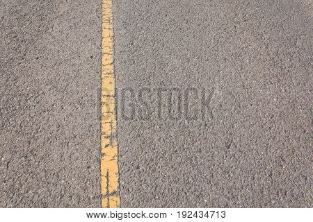 Yellow lines is painted on the asphalt road.