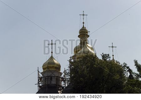 Christian orthodox white church with gold domes and crosses. Restoration