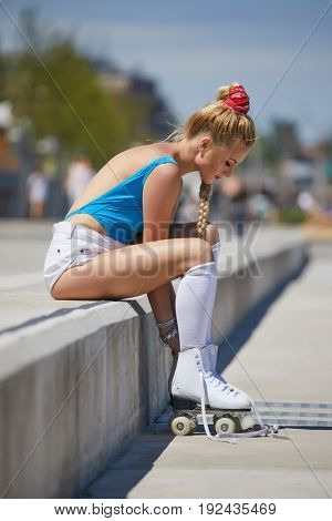 Gorgeous blond girl in a swimsuit on roller skates sitting in a city park banks of the river. Sunny summer day in Europe.