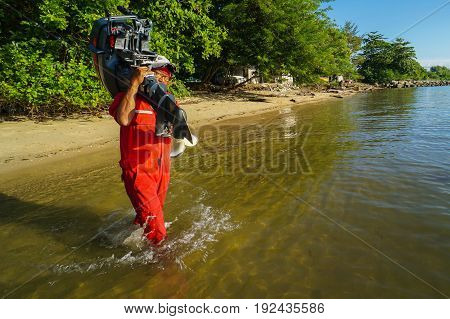Labuan,Malaysia-June 10,2017:Morning scene of daily activities in fisherman village,fisherman carrying an outboard motor on his shoulder,to install in fishing boat,ready to fishing in Labuan,Malaysia.