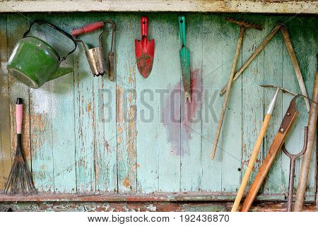 Old dirty farm gardening tools, spade, fork and rake on wooden wall. Vintage equipment, background
