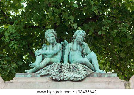 Bronze statue of two cupids sitting in Copenhagen Denmark