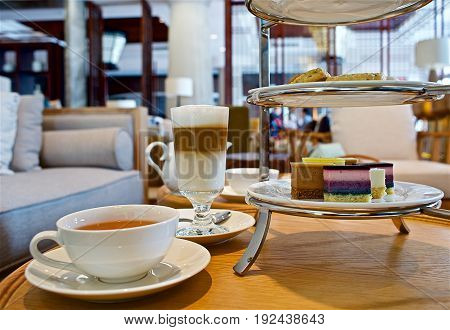 Table with cup of black tea, glass of latte macchiato and cakes