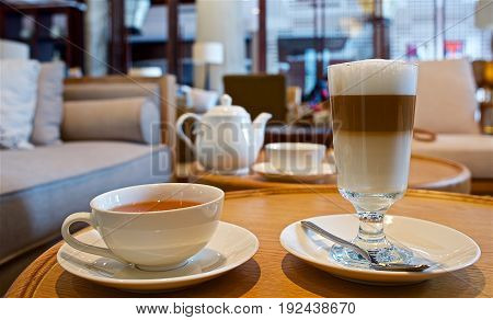 Table with cup of black tea and a glass of latte macchiato in a cozy environment