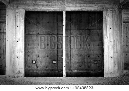 Empty concrete elevator shaft in abandoned building. Black and white.