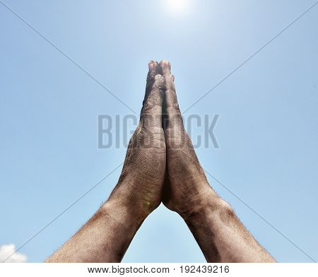 Two male hands folded in prayer gesture on sky background