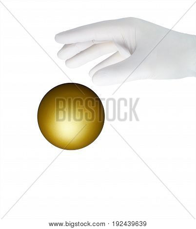 A hand in a white glove grabs a golden ball.