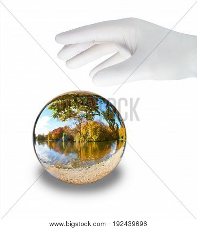 A hand in a white glove grabs a glass ball with a landscape.