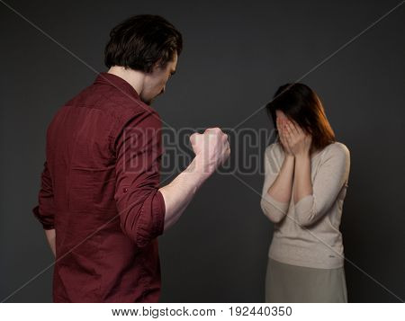Violence in the family, man is threatening a woman with the fist, she is frightened, gray background