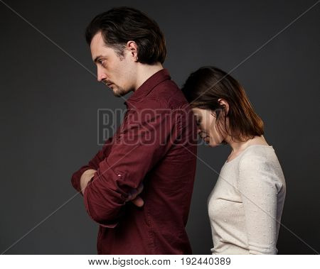 Family quarrel, woman rests her forehead in the back of her husband, gray background