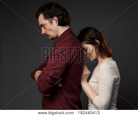 Family quarrel, woman is touching the back of her husband, gray background