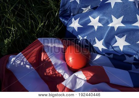 Red heart and American flag on the grass