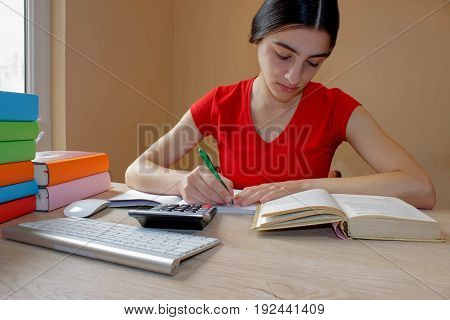 Student Young Girl write in notebook between books. Girl working on his homework. young attractive student Girl studying lessons