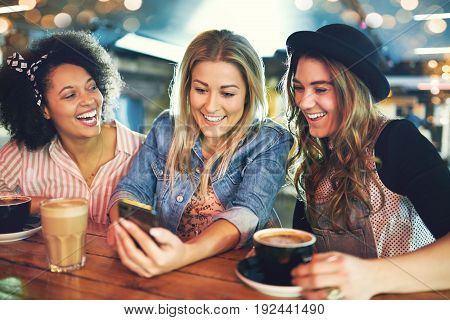 Three Young Girlfriends Relaxing Over Coffee