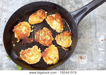 Vegetable patties  with cauliflower, chickpeas and oatmeal in a black frying pan.