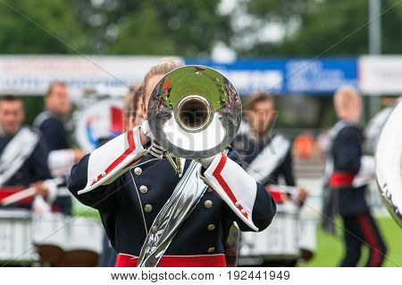 Details from a music show and marching band. Playing musicians wind instruments in uniforms. Baritone Mellofoon.