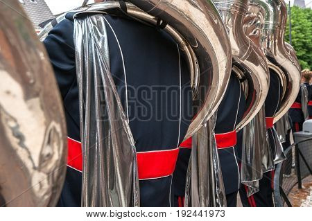 Details from a music show and marching band. Playing musicians wind instruments in uniforms. Tuba Sousa