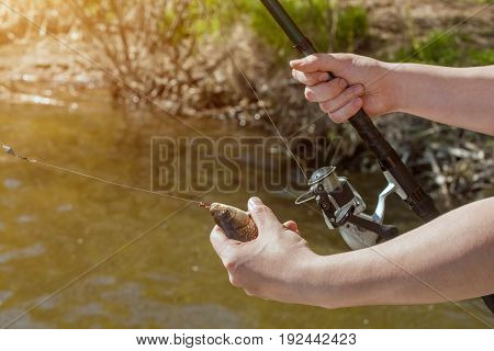 The fisherman is holding a fish caught on a hook in a freshwater pond.