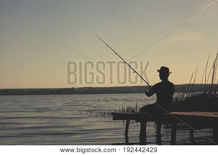 A fisherman on the river bank sits on a wooden bridge and catches fish.