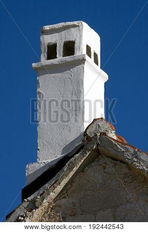 White painted chimney on old mediterranean stone house in Croatia on island Brac