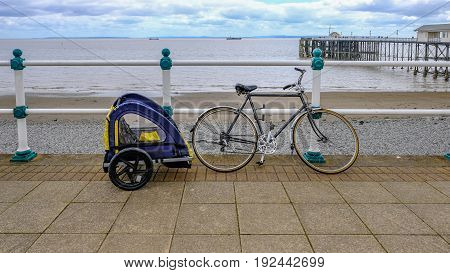 Bike with child cycle buggie secured to railing on the sea front. Shows beach and sea and pier in the background.