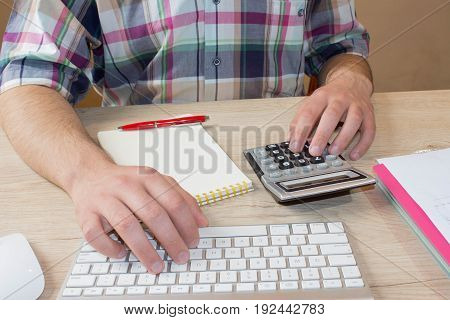 Businessman working on office desk with Calculator a computer a pen and document. Man counting money and making calculations